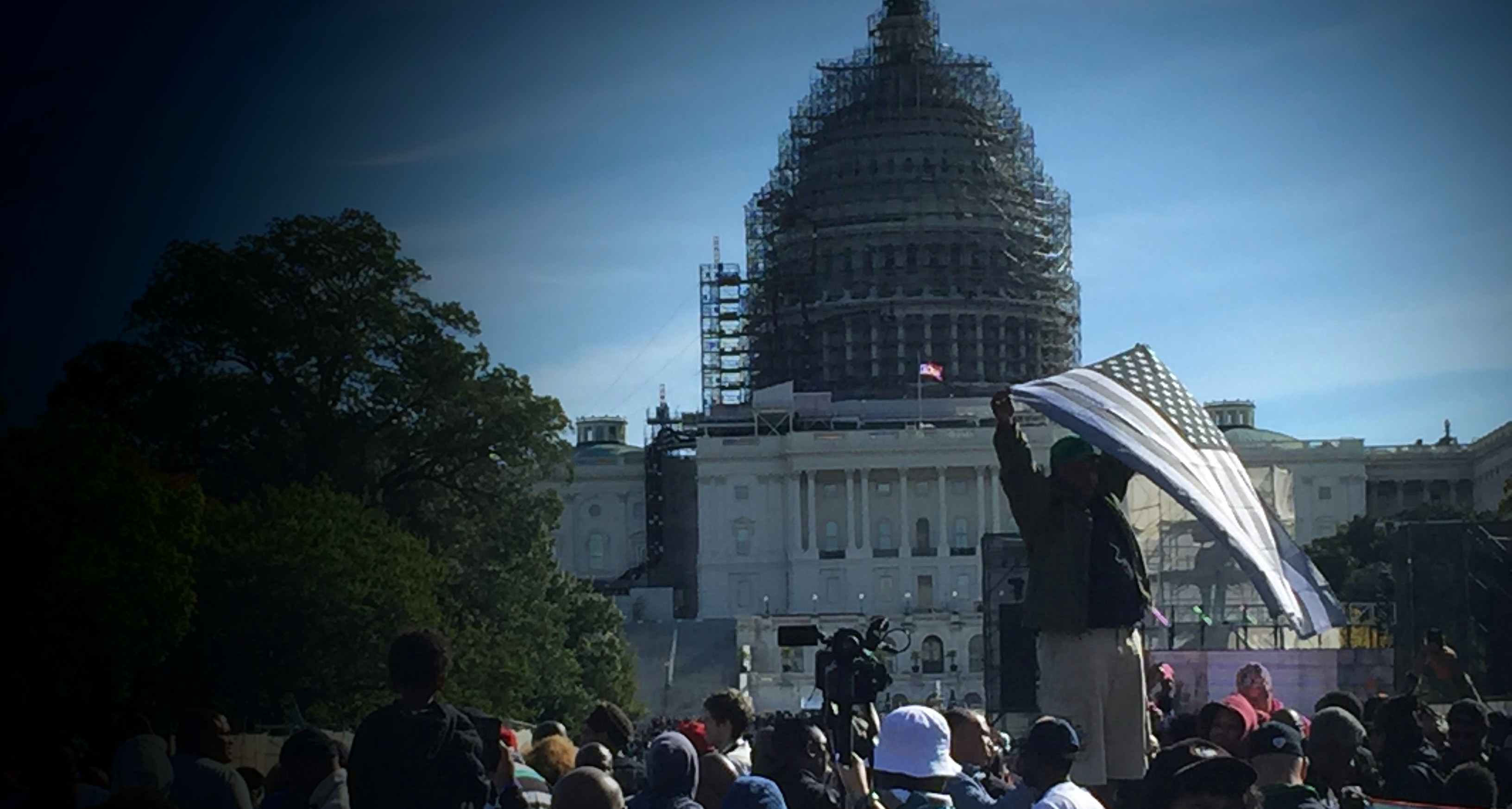 The Million Man March, October 10, 2015. A man holds a faded American flag, symbolizing America failing its citizens and existing in a state of faded glory.